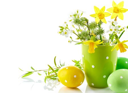 Easter eggs with bunch spring flowers narcissus blooming branch willow. Festive composition side view. Isolated on white background.