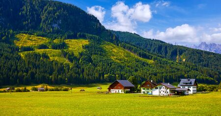 Austrian village among meadows fields and Alpine mountains. Knolls covered with forests and blue sky with clouds. Picturesque summer landscape from Austria.