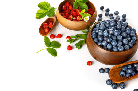 Berry blueberry and wild strawberry in wooden dish with green leaves and flower. Fruity still life. Healthy eating, isolated on white background. Standard-Bild