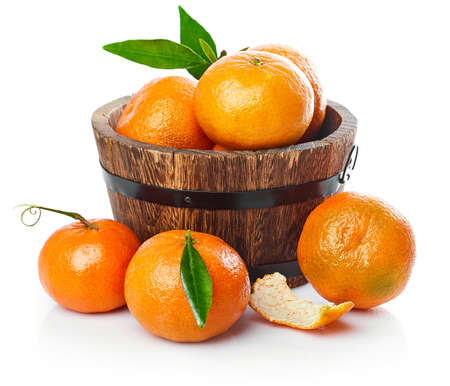 Harvest tangerines in wooden basket with green leaves. Fruity still life with fresh fruit. Isolated on white background.