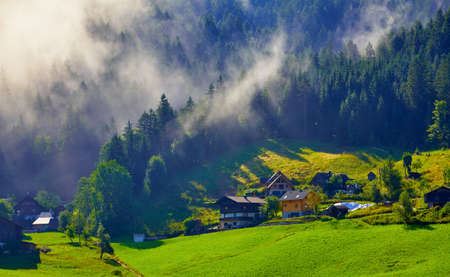 Austrian Alps Mountains. Alpine Village in forest and lawns with green grass. Foggy clouds on the trees. Traditional alpine village houses on the hills. Sunny morning