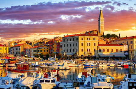 Rovinj, Istria, Croatia. Motorboats and boats on water in port Rovigno. Medieval vintage houses of old town. Yachts landing, high tower of Church of Saint Euphemia. Morning sunrise blue sky withclouds.