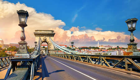 Chain bridge in Budapest, Hungary. View at Royal castle at Buda district over Danube river. Antique street lanterns along road and stone arcs. Summer urban landscape with sunset dramatic sky with clouds.