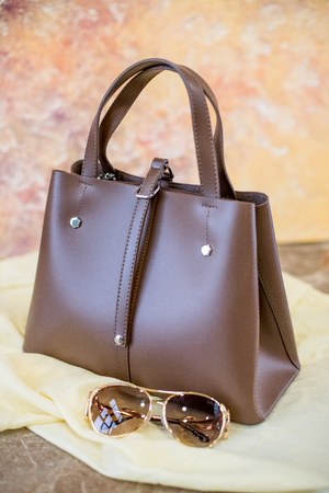 Woman Accessories Isolated on yellow Background.leather bag and sun glasses.beautiful brown shoulder bag and sun glasses