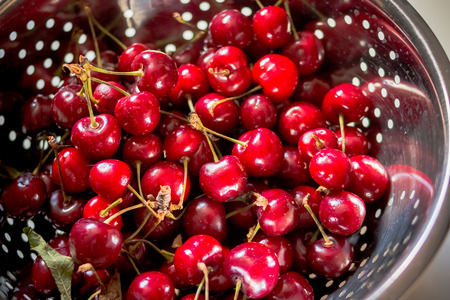 Fresh ripe cherry in colander at sunny morning.Metal strainer with sweet red berries and cherry on wooden background.