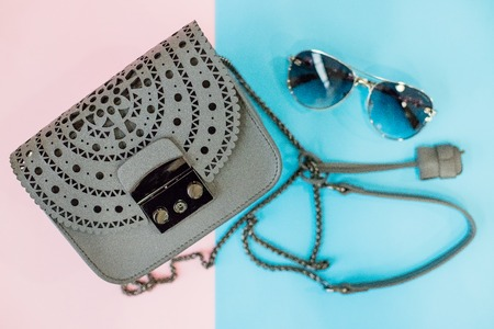 girls handbag, sun glasses on a light background.Fashionable womans leather grey tote with sunglasses.Vintage leather bag isolated on a pink. blue background.