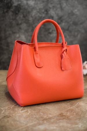 Stylish womens handbag Isolated on a stone background. Orange, light coral. Clothing and accessories.Elegant outfit Fashion concept.Luxury female handbag