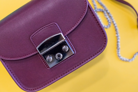 Purple Womens handbag, Ladies bag, Purple female clutch, Purple clutch.Womens bag isolated on yellow background. Stock Photo