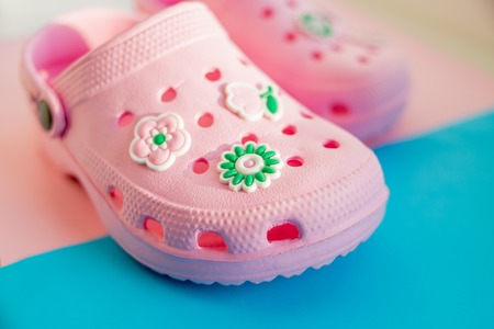 Colorful childrens rubber sandals isolated on the blue background. pink rubber shoes.Childrens shoes