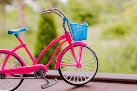 Small pink bicycle model on the handrail with garden background.Green transport.Vintage bicycle,selective and soft focus. Copy space