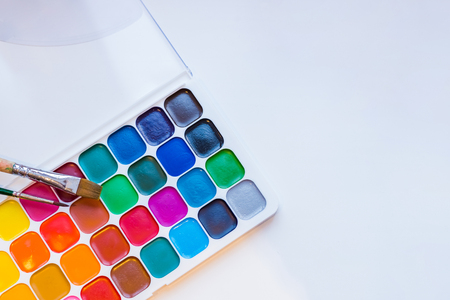 Tools for creative work on a white wooden background. Watercolor paintbox. Color paints . Back to school. Kids painting concept. Children art. Top view. Copy space.