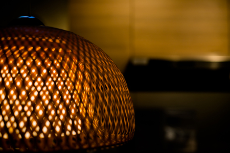 Close Up of Luxury Woven Bamboo Lamp with Yellow Light Inside.Openwork wicker lampshade.old fashion lamp. Copy space