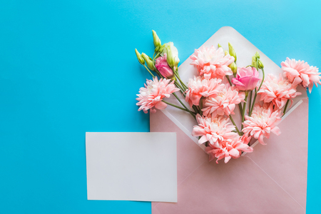 Styled feminine flat lay on blue candy background, top view.Minimal womans desktop with blank page mock up, envelope, pink lisianthus, chrysanthemums. Creative concept, greeting card.Copy space