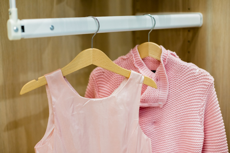A row of children clothes hanging on hangers. Fashion for girls.Wardrobe with kid clothes.wooden Hangers with pink clothes. Set for girl