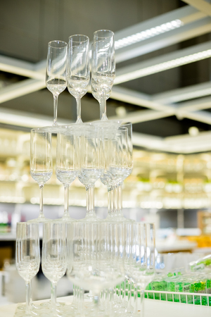 empty glasses in pyramid or tower on table at wedding reception, alcohol bar, catering in restaurant.Pyramid of champagne glasses Stockfoto