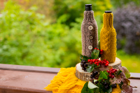 Peaceful Fall berries, Leaf, Acorn, scarf as Still Life on Rustic Wooden Cut Tree Trunk and nature Background.
