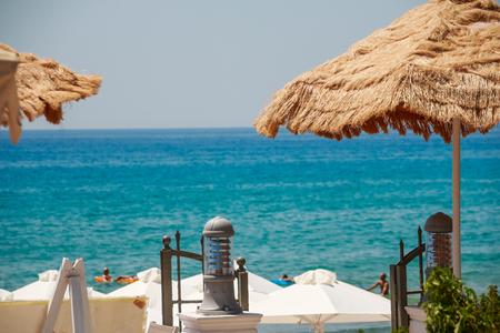Summer Seaside Restaurant Terrace or Veranda Interior, Flattering Curtains, Metal Lanterns, White Wooden Furniture, Sea View.