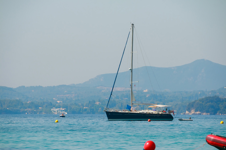 Seascape with sailboat the background of the blue sky and mountains.
