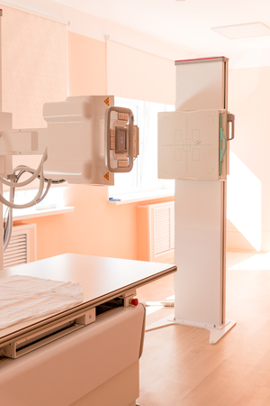 An x-ray machine with x-ray table in a hospital.X-ray equipment in medical center. Breast cancer. Medical machine in an examination room.Medical-diagnostic equipment room. Stock Photo