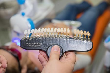 Medicina, odontoiatria e concetto di assistenza sanitaria - Chiuda in su del dentista con campioni di colore del dente scegliendo l'ombra per i denti del paziente maschio presso la clinica odontoiatrica Archivio Fotografico