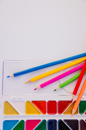 Tools for creative work on a white wooden background. Watercolor paintbox. Color paints and pencils. Back to school. Kids painting concept. Children art. Top view. Copy space.
