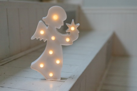 Christmas angel with lamps on dark white background.nightlight in the shape of angel in the childrens room.Lamp, kids night light in the childrens bedroom.little white guardian angel isolated. vintage style Banco de Imagens