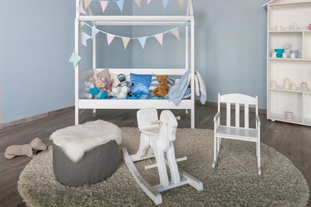 wooden horse in a kids boy room interior.Stylish furniture in a monochromatic spacious kids room.Modern stylish childs bedroom interior with a small decorated babys bed.traditional rocking horse toy Archivio Fotografico