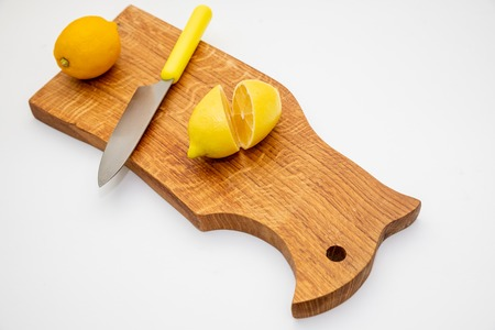Sliced fresh lemon over chopping board.environmentally friendly, ecological products.prevention of colds.Sliced and whole lemons on cutting board with a knife .Copy space