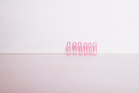 office supplies.The composition row of multi-colored paper clips on pnk, pastel background.Colorful paper clips isolated.Copy space.Creative composition.Minimalism concept.Arts and crafts material