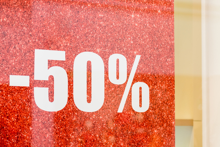 Special sale up to 50 off text on a glass wall, a view inside the popular clothing store.The final sale, 50,clothing boutique. discounts.sale 50 off mock up advertise display,shopping, business and advertisement concept Archivio Fotografico