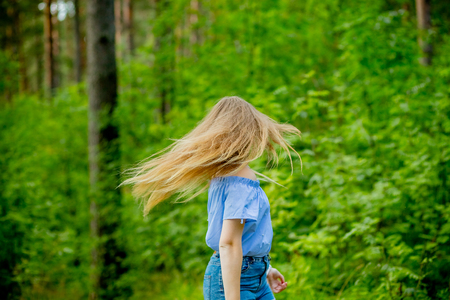woman in blue blouse with long fluttering hair on nature background.Positive human emotions.long hair fluttering in motion.Young woman dancing in wild forest nature.girl flipping her hair from the back view.