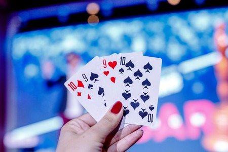 Closeup of four playing cards showed by womans hand with blurred background. Symbol of winner.Poker card game.combination of playing cards poker casino.People having fun while playing game