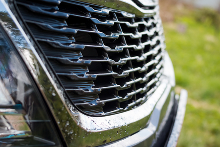 Grid of car. Radiator grille. Metal close-up texture background. Chrome grill of big powerful engine macro. Auto detail.Selective focus