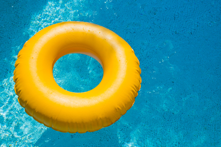 floating ring on blue water swimpool with waves reflecting in the summer sun. Lazy river.Water pool with yellow pool float ring.Summer vacation or trip safety item. Top view swimming circles.rubber ring for swim