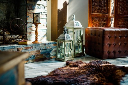 interior with vintage brown leather sofa,pelt of bear, candles and lanterns in loft room with sunlaight, copy space.interior decor. White decorative wooden latern lights in expensive interior like Swiss chalet.