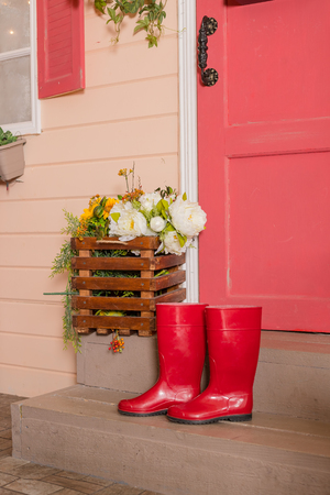 Red rubber shoes on the steps of the house.women water-proof boots.bright red gardening boots.trendy shoe for Rainy day spring, autumn fashion, boots for rainy weather.wellington boots