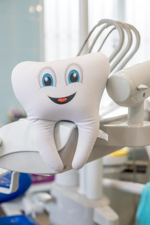 Teeth smile emotion with dental mirror tool isolated on blue background, With clipping path teeth and tool.smiling tooth toy in Modern dental cabinet.childrens stuffed toy idea. Im not afraid by dentist clinic