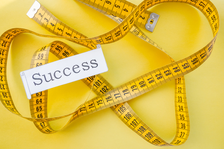 yellow measuring tap ,diet, dream to be slim, healthy concept, results of fitness jogging and sticking to healthy lifestyle.success. measuring tape and word success - conceptual.dream of a beautiful figure Stok Fotoğraf