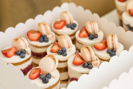 Various mini cakes. Sweets decorated with fresh berries for holiday.tasty cake.small cakes with various berries and vanilla cream, berries and Colorful macarons .Macaroon is sweet meringue-based confe 스톡 콘텐츠