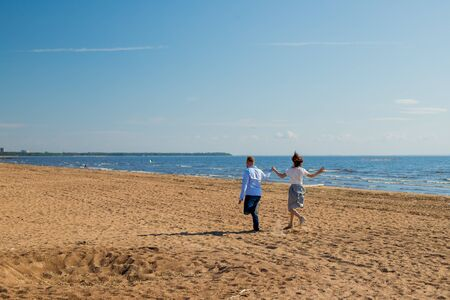 Man and woman dancing, couple happy on vacation. Couple in love running on beach, seashore. happy young wedding couple of man and woman running along sea beach coast on windy weather sunny day Stock Photo