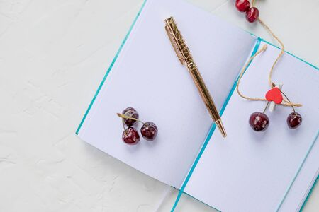 Flat lay arrangement of empty notebook journal with pen next to fresh berries on white background, top view.Notebook and red hearts isolated ,copy space. planning for Valentine day, love and romance concept.