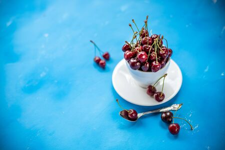 Creative composition of fresh ripe cherry in a wite cup with copy space isolated on blue background minimal style. Concept of summer fun and healthy eating. Template for your text or food design