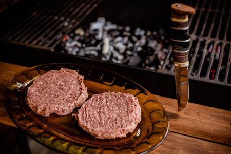 raw ground beef meat hamburger patties on paper, dry pepper.raw beef or pork meat barbecue burgers for hamburger cooked grilled on bbq grill.Healthy food, cooking concept.