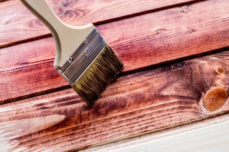 brown color painting on wooden table or fence or wall, or floor, use for home decorated. House renovation. Half - painted surface. Smear of paint brush. House renovation. painted surface. brush.