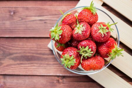Appetizing strawberry in the bowl Isolated on wooden background.Summer vitamins.Diet food.Sweet fresh juicy organic ripe strawberries on wooden surface.healthy food photo.Copy space