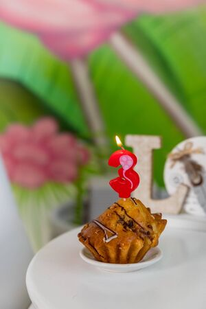 Birthday candle in shape of number in muffin.Number three birthday candle on cupcake on a white table. Birthday cupcake with chocolate