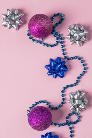 Christmas beads and ornaments on pink. New Year balls, confetti. Winter holidays preparations. Top view. Minimal festive card.silver and blue bow with decoration and sparkles. Festive concept.