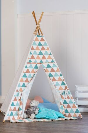 Decorative boho styled cozy hut with decor. Wigwam in room, Scandinavian style, minimal home interior design.tent for the child in the room.Cozy kids room interior with play tent and toys Stockfoto