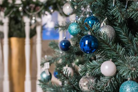 Beautiful illuminated christmas tree in a living room. Luxury living room interior decorated with chic Christmas tree. Blue and silver christmas ornaments, balls, tinsel.