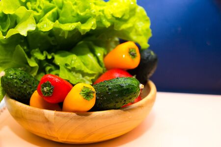fresh vegetables and herbs in a wooden bowl isolated on a white blue background. Healthy salad food. Lost weight food concept. copy space